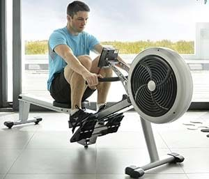 Man working out with JTX Freedom Air Rowing machine