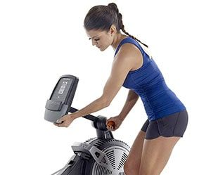 Woman adjusting monitor dispaly of Nordic Track RX800 rowing machine
